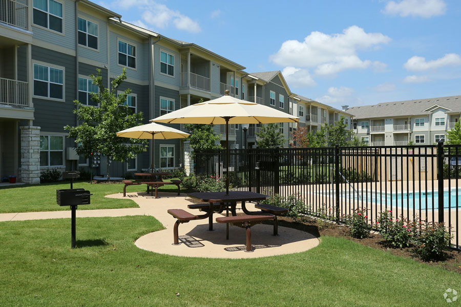 Outdoor seating area with benches and umbrellas at The Villages at Ben White