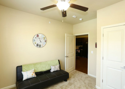 Bedroom with carpet flooring, black couch, and a clock on the wall