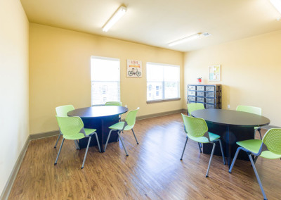 Craft room at the Villages at Ben White with round tables and green chairs