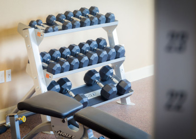 Free weights and a workout bench inside the fitness center at the Villages at Ben White