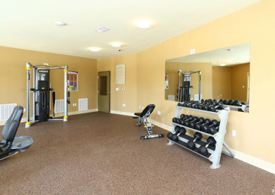 Villages at Ben White fitness center with free weights and a cable machine