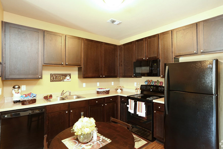 Kitchen at the Villages at Ben White senior apartments with brown cabinets and black appliances