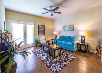 Living room with a teal couch, brown area rug, dark brown coffee table, and a ceiling fan