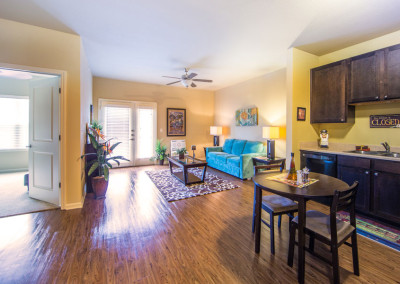 Open floor plan layout of the Villages at Ben White senior apartments showing the kitchen flowing into the living room