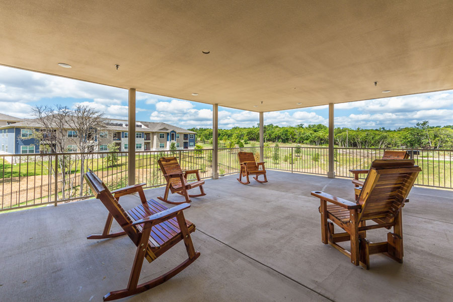 The Villages at Ben White patio area with wooden rocking chairs