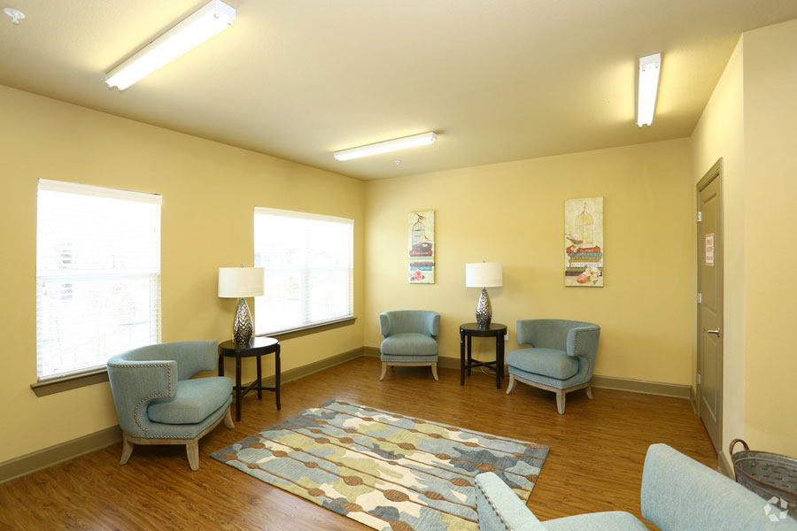 Villages at Ben White reading room with 4 light blue lounge chairs and an area rug in the middle